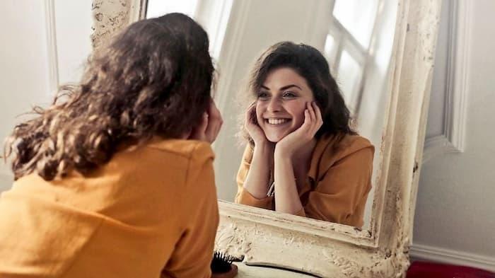 Mujer mirandose en el espejo con el metabolismo acelerado