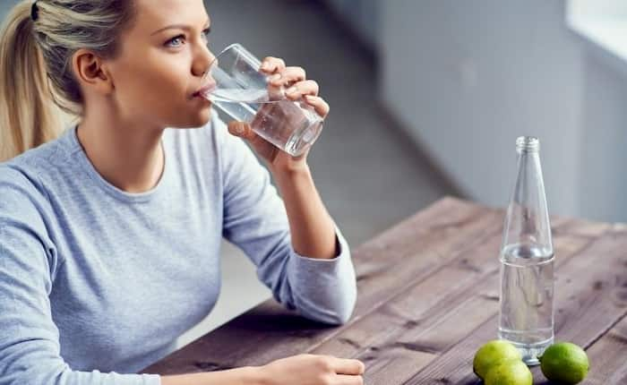 mujer bebiendo agua con limon